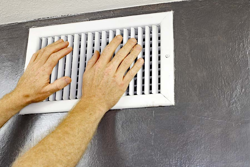 ac unit blowing hot air, a pair of adult male hands feeling the flow of air coming out of air vent feeling for air flow