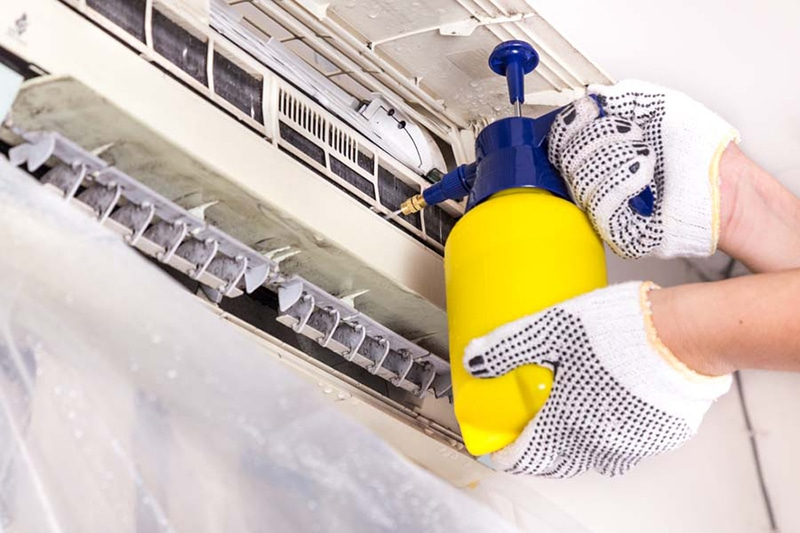 AC Maintenance Checklist | Air Conditioning | Happy Valley, OR, Technician spraying chemical water onto air conditioner coil to clean and disinfect