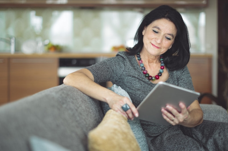 woman smiling on couch with ipad